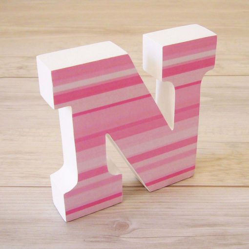 letra n de madera con rayas rosas