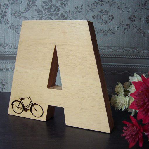 Letra A grabada con bici hecha en madera natural
