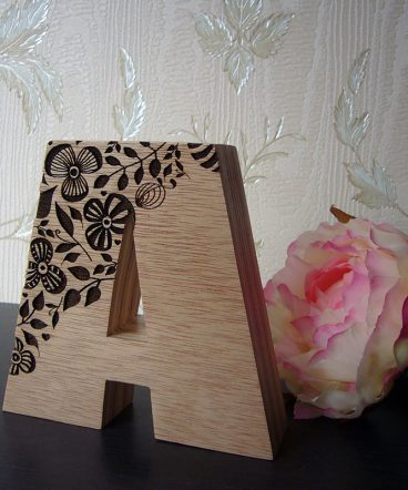 letra a de madera con flores grabadas